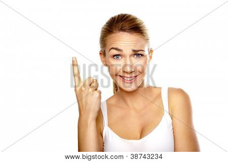 Beautiful confused woman with a raised eyebrow and quizzical expression pointing with her finger above her head isolated on white