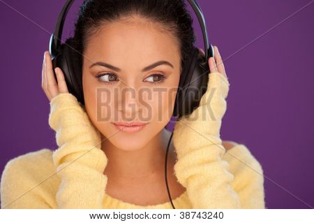 Beautiful woman immersed in her music listening intently to the tunes on a pair of stereo headphones