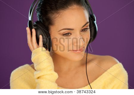 Beautiful woman wearing stereo headphones listening to music against a purple background