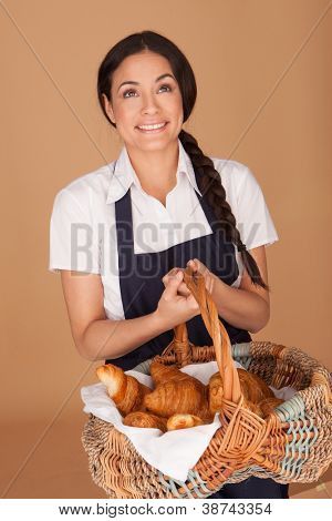 Happy beautiful brunettte woman carrying a wicker basket full of freshly baked crisp golden croissants
