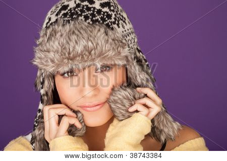 Pretty woman in a fur trimmed winter hat snuugling into the warmth of the earflaps against the winter chill