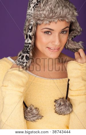Beautiful woman in warm winter hat with ear flaps and pom-poms trimmed with fur