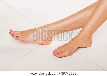Tanned bare female feet with varnished toenails on a white background conceptual of podiatry, beauty, glamour , hygiene and body care