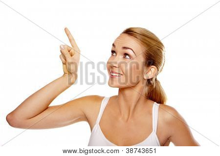Excited attractive blonde woman pointing above her head with her finger towards blank copyspace isolated on white