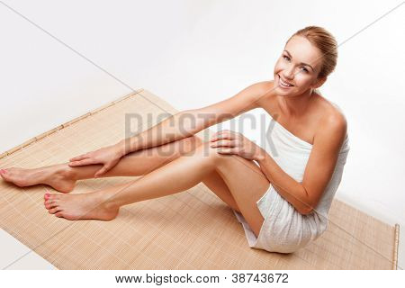 High angle clean fresh portrait of a beautiful naked young lady wrapped in a bath towel sitting on a reed mat over a white background