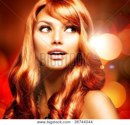 Beautiful Woman With Shiny Red Long Hair over Blinking Holiday Background.Surprised Girl