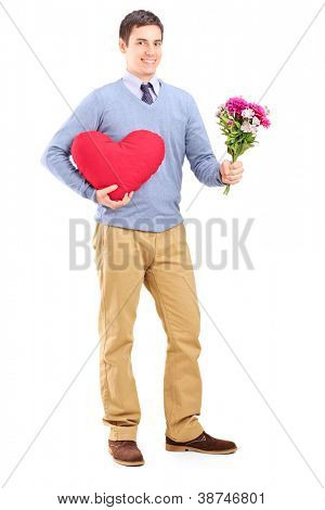 Full length portrait of a young man holding flowers and red heart isolated on white background