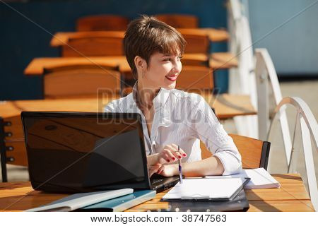 Young business woman with laptop at a sidewalk cafe