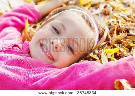 Closeup portrait of a smiling girl lying on yellow leaves