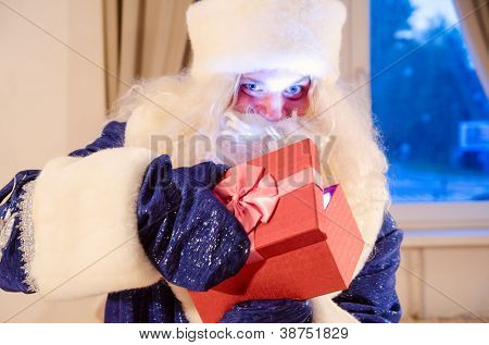 santa claus is opening a gift box