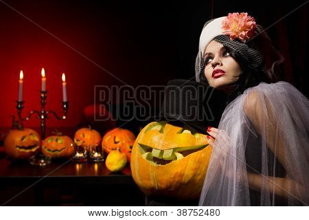 Beautiful sexy woman with halloween pumpkins over red background