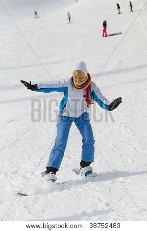 Young laughing woman with snowboard on the snow