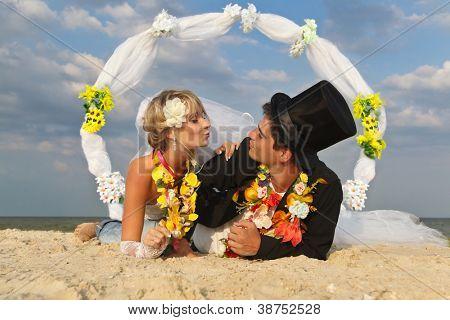 Groom with bride wearing lei lying on beach