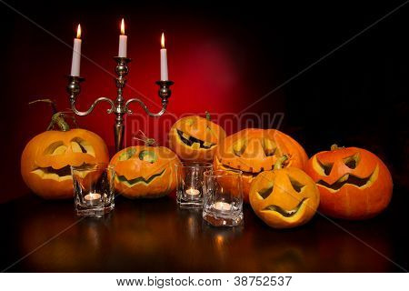 Halloween pumpkins with candelabra on a wooden desk over red background