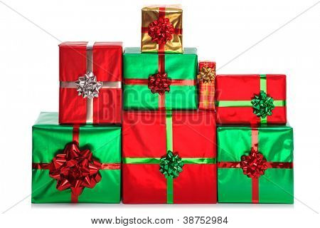 A group of gift wrapped presents in bright shiny wrapping paper with bows and ribbons, isolated on a white background.