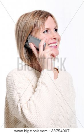 Caucasian middle aged woman on cellphone smiling over white background