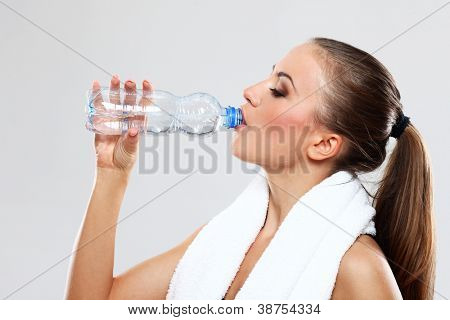 Fitness woman drink water after train on grey background