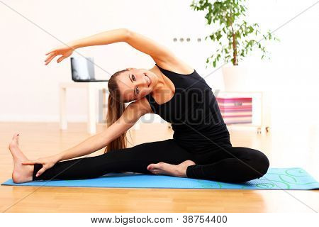 Happy and beautiful woman do yoga exercises at home on blue mat