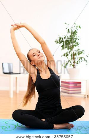 Young and beautiful woman do yoga exercises at home on blue mat