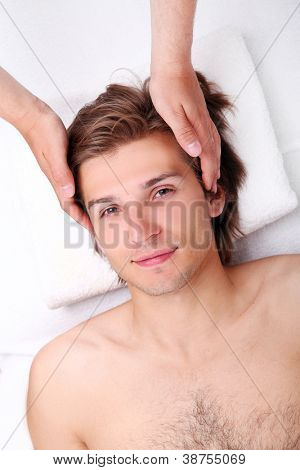 Closeup of Handsome man enjoying face massage in spa salon