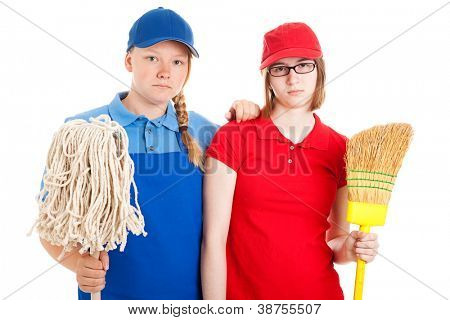 Two serious looking teenage girls, dressed in uniforms for menial jobs and holding a broom and mop.  Isolated on white.