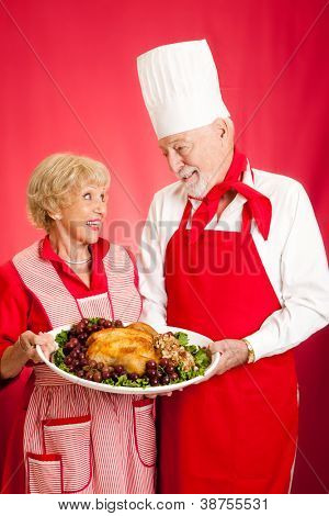 Chef and homemaker collaborated on making a delicious holiday turkey dinner.  Red background.