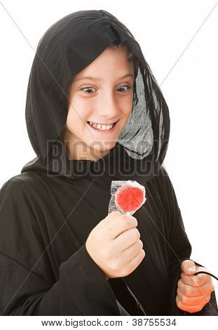 Little boy dressed in his halloween costume, looking hungrily at a lollipop.  Isolated on white.
