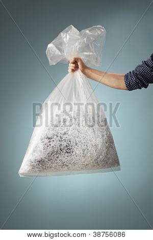 Man holding a transparent plastic bag with shredded paper.
