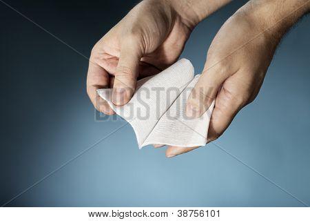 Hands holding a sterile medical textile gauze bandage.
