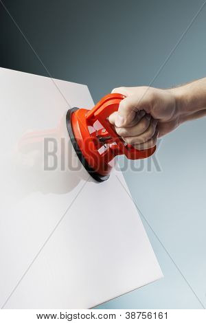 Man lifting a white ceramic tile using a vacuum suction cup tool aka dent puller.