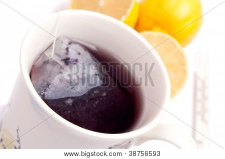 Full cup of tea and blurred lemon and thermometer in the background