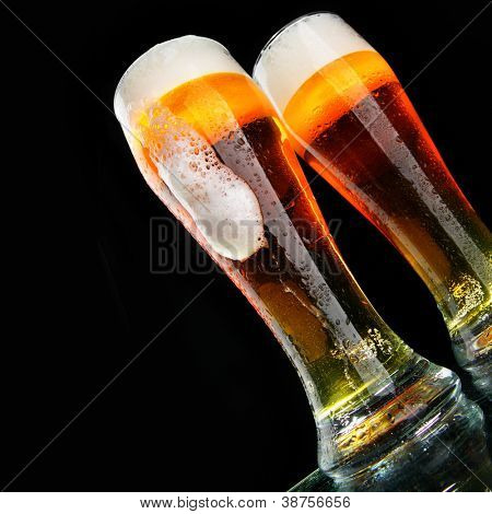 Glasses of beer with froth over black background