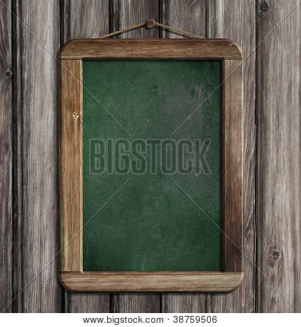 Aged green menu blackboard hanging on wooden wall