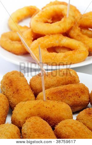 closeup of some plates with spanish croquettes and calamares a la romana, breaded and fried rings of squid, on a white background