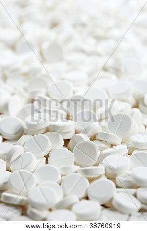 Pharmacy theme, Heap of white round medicine tablet antibiotic pills. Shallow DOF