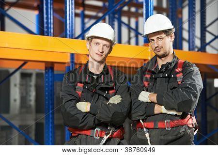 Two warehouse installation staff male workers in uniform in front of pallet rack arrangement stillages