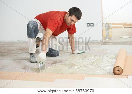 Worker carpenter doing parquet Wood Floor work gluing down cork padding layer