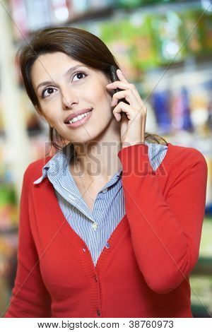 Young woman smiling and speaking on phone during shopping at supermarket store