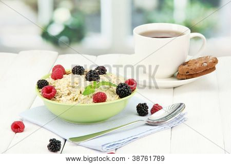 tasty oatmeal with berries and cup of tea on table, on window background