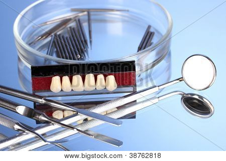 denture with dental tools on blue background