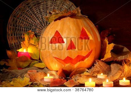 halloween pumpkin and autumn leaves, on wooden background