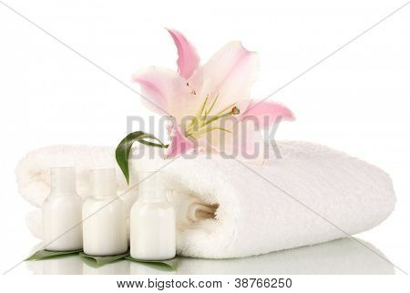 beautiful lily with towel and bottles isolated on white