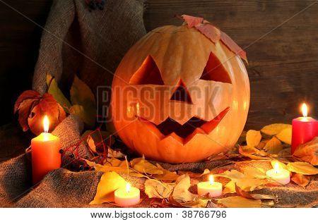 calabaza de Halloween y hojas de otoño, sobre fondo de madera
