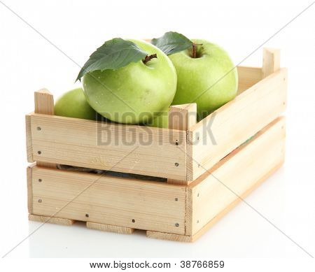 Ripe green apples with leaves in wooden crate isolated on white