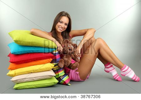 beautiful young girl and fluffy bear with pillows on grey background