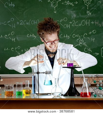 Laughing mad professor combines some liquids in his laboratory