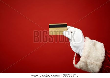 Photo of Santa Claus gloved hand holding credit card