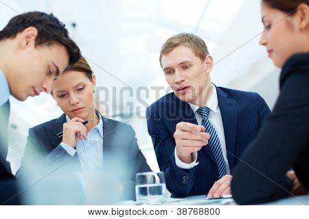 Attentive business partners listening to new ideas and thinking them over at meeting