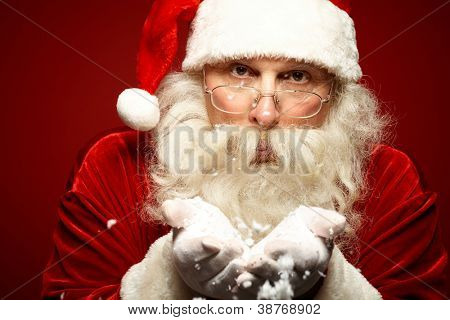 Photo of Santa Claus in eyeglasses blowing snow and looking at camera