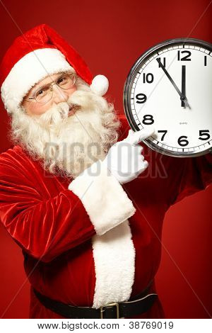 Photo of Santa holding clock showing five minutes to midnight